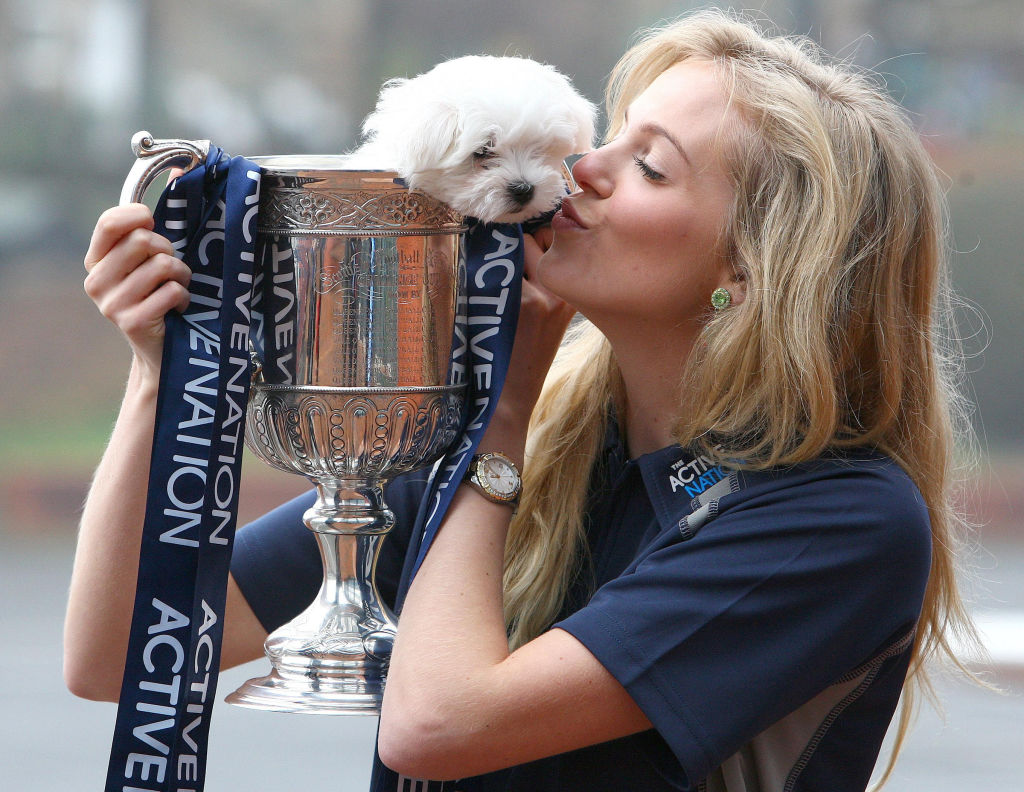 amaltese puppy inside a trophy held up by Miss Scotland, Katharine Brown