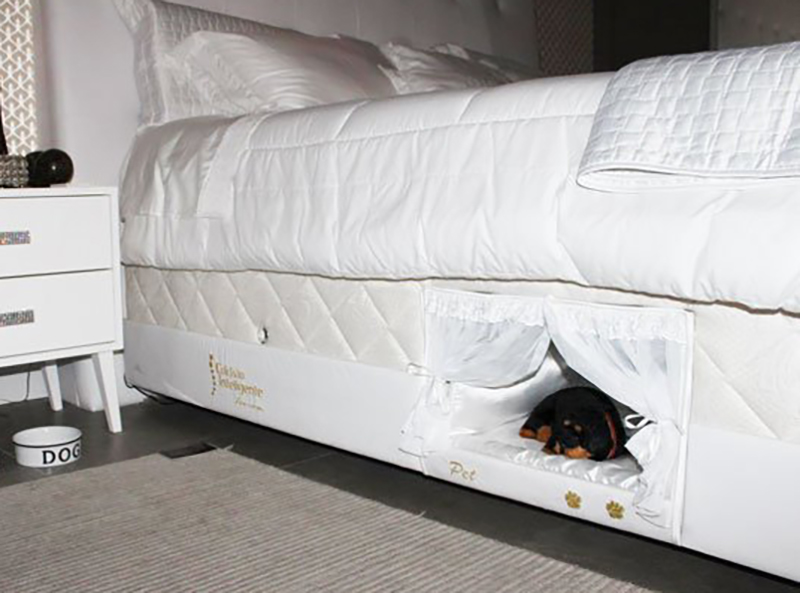 A doggy bed is built into its owner's bed